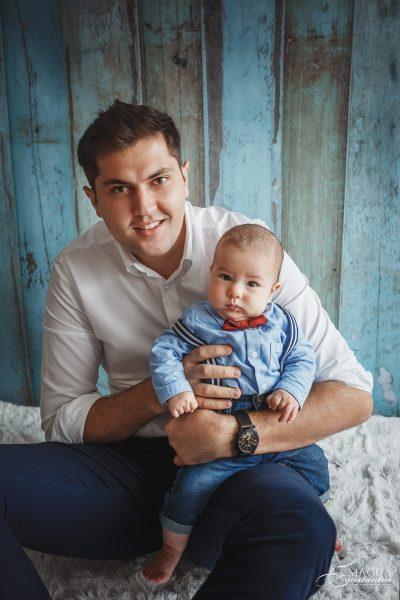 Sedinta foto de bebelus cu Radu in studio, tatal cu bebelusul in brate in camasi pe fundal de lemn albastru