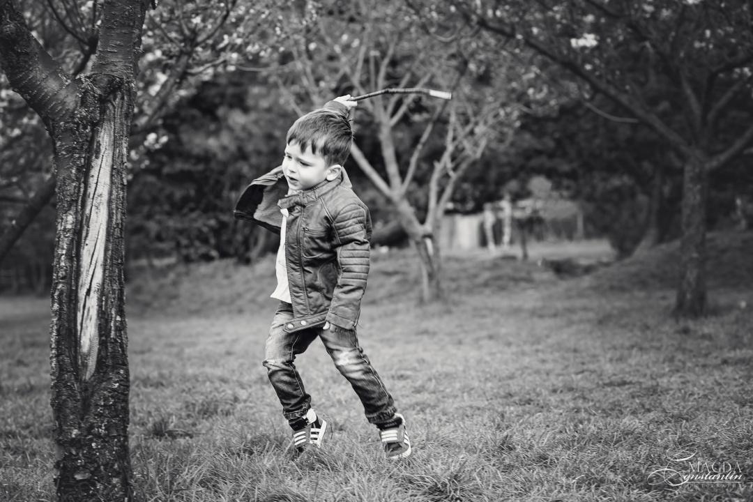 baietel alergand cu un bat, alb-negru