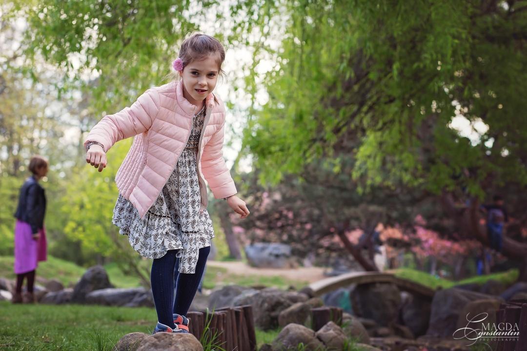 fetita cu geaca roz mergend in echilibru pe un sir de pietre