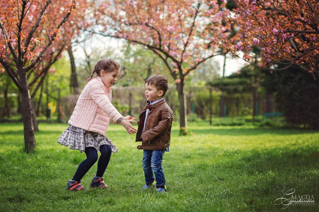frate si sora jucadu-se in gradina japoneza din herastrau, primavara, cu ciresi infloriti