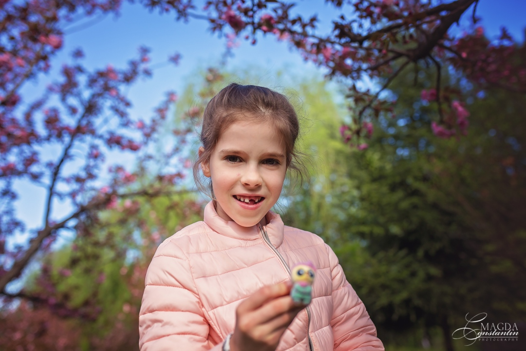 sedinta foto de familie in herastrau, primavara, fetita zambind in geaca roz tine o floare de cires in mana